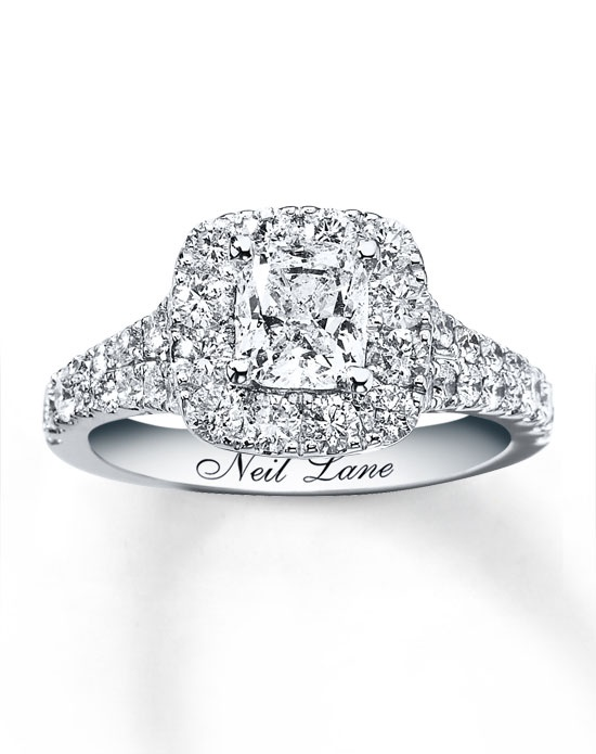 Breathtaking round diamonds surround a cushion-cut diamond in the romantic engagement ring as part of her bridal set from the Neil Lane Bridal® collection. The band is awash with additional round diamonds for a dramatic effect. The brilliant matching wedding band features a line of glittering round diamonds and is contoured to fit around the engagement ring. The bridal set has a total diamond weight of 2 1/2 carats and each ring features Neil Lane's signature inside the 14K white gold band. Diamond Total Carat Weight may range from 2.45 - 2.57 carats.