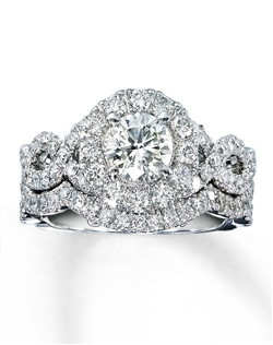 Reminiscent of Hollywood's most glamorous era, designs by Neil Lane are as contemporary as they are nostalgic. Here, a stunning round diamond emerges from a circle of round diamonds, as additional round diamonds weave a pattern to accentuate the center. The matching wedding band hosts a line of round diamonds. Each Neil Lane Bridal® ring is hand-crafted and undergoes a four-step polishing process which gives the ring its beautiful shine and luster. Two carats of diamonds, set in 14K white gold with Neil Lane's signature inside each band. Diamond Total Carat Weight may range from 1.95 - 2.11 carats.