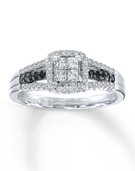 A frame of round white diamonds surrounds four princess-cut white diamonds at the center of the breathtaking engagement ring in this bridal set for her. The band is adorned with more round white diamonds and round Artistry Black Diamonds™ for dramatic contrast. The matching wedding band features a row of round white diamonds and is contoured to fit around the engagement ring. The bridal set, styled in 10K white gold, has a total carat weight of 1/2 carat. Artistry Black Diamonds™ are treated to permanently create the intense black color. Diamond Total Carat Weight may range from .45 - .57 carats.