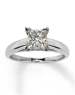 A ravishing independently certified 1 1/2 carat princess-cut diamond takes center stage in this captivating engagement ring for her. This ring is fashioned in 14K white gold. Diamond Total Carat Weight may range from 1.45 - 1.57 carats.