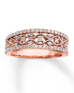 This vintage-inspired anniversary ring for her features lattice work styled in 10K rose gold with a milgrain design and round diamonds. More round diamonds line the top and bottom of the ring for an awe-inspiring finishing touch. The ring has a total diamond weight of 1/2 carat. Diamond Total Carat Weight may range from .45 - .57 carats.