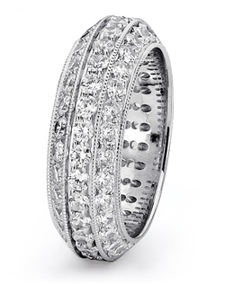 Steeped in tradition and designed to emanate the warmth, the sparkle and the light of diamonds in a pave set bridal jewelry collection. Featured is a 14K white gold eternity band sparkling with 3.00tcw of  round diamonds, finished with milgrain edges. All from the Love is Light collection. Available in platinum and gold.