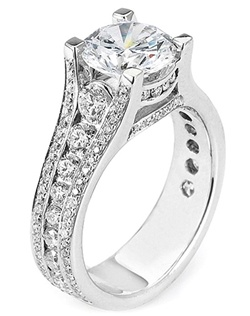 This diamond engagement ring features graduated round brilliant cut diamond channel set going down the shank in between two rows of pave set round brilliant cut diamonds. Along the basket are also pave set round brilliant cut diamonds which compliment your choice of center diamond.