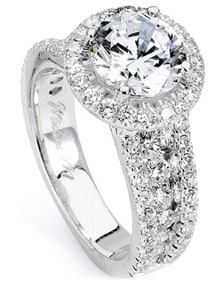 This diamond engagement ring by Michael M. features three rows of pave set round brilliant cut diamonds down the shank as well as a single row around the center stone of your choice.