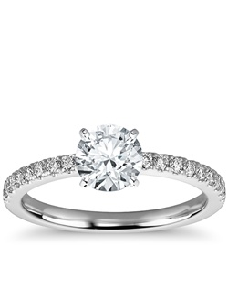 Delicate and beautiful, this diamond engagement ring in platinum features a half circle of sparkling petite pavé diamonds to complement your center diamond. Setting includes 1/4 carat total diamond weight. Price listed below is for the setting only.