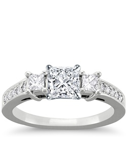 Elegant in design, this petite diamond engagement ring showcases ten round pavé-set diamonds with two princess-cut side diamonds and your diamond of choice set in 14k white gold. Setting includes 1/3 carat total diamond weight. Price listed below is for the setting only.