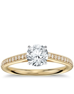 Elegant with a touch of vintage, this diamond engagement ring setting features pavé-set diamonds in a delicate 18k yellow gold milgrain design to frame your center diamond. 1/8 carat total diamond weight. Price listed below is for the setting only.