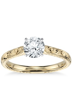 Exquisitely hand-engraved, this engagement ring features an intricate motif to showcase your center diamond in enduring 18K yellow gold. Price listed below is for the setting only.