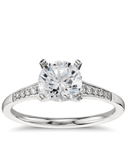 Ideal for any center diamond of your choice, this platinum engagement ring showcases a diamond accent along the shank and milgrain detailing. Price listed below is for the setting only.