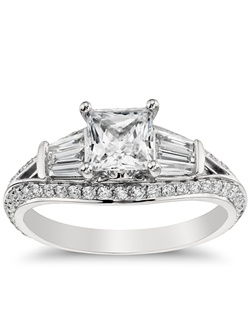 Alluring in every way, this intricate platinum engagement ring showcases a distinct tapered design, baguette and round pavé-set diamonds, and a pink sapphire that accents its graceful aesthetic. Price listed below is for the setting only.