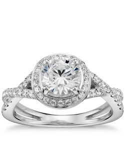 Lavishly curved and showcasing your center diamond with brilliance, this twist-shank halo engagement ring is crafted in enduring platinum with scintillating pavé set diamond accents. Price listed below is for the setting only.