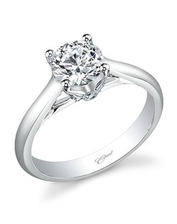 From the Coast Romance Collection, this elegant solitaire engagement ring is made for a 1CT round center stone and is adorned by a peek-a-boo diamond under the head. Diamond weight .02CT.