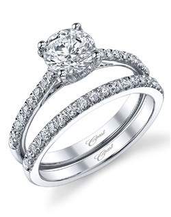 This timeless Charisma engagement ring design features petite diamonds decorating the shoulders of the ring, and a 4 prong setting for the 1CT center stone. A matching band completes the look.