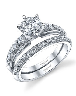This beautiful engagement ring features graduated diamonds cascading down the shoulders of the ring, and a traditional 6 prong setting for the 1CT center stone. Shown with matching diamond band.