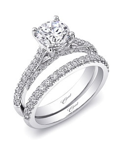 Simple yet stunning, this engagement ring is decorated with brilliant diamonds on the shoulders of the ring. Ribbons of pave set diamonds in the gallery add excitement to this traditional design. A matching band completes the look for a unique wedding set. Created for a 1CT center stone.