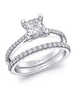 A classic engagement ring featuring a 5.5mm princess cut center stone and diamonds down the shoulders of the ring. Shown with matching diamond band.