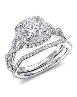 This sophisticated engagement ring features a cushion shaped halo of diamonds, framed by strings of diamonds which twist down the sides of the finger. Shown with a 1CT center stone. The matching diamond band is contoured to fit perfectly against the engagement ring, creating a stunning wedding set.