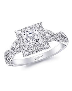 This chic engagement ring features a 5mm princess cut center stone, surrounded by a square diamond halo. Twisting strands of diamonds cascade down the sides of the ring.