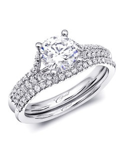 This exquisite and unique engagement ring features a double row of diamonds on the shoulders of the ring, which splits to surround the 1CT center stone. Shown with contoured matching band.