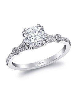 This delicately designed engagement ring features petite diamonds on the shank and double prongs holding a 1CT center stone.