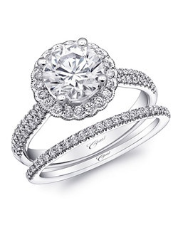 From the Charisma Collection, this unique engagement ring features a halo of diamonds surrounding the center stone, complete with milgrain edging. Two rows of petite diamonds add sparkle to the shoulders of the ring. Created for a 1.5CT center stone. Shown with matching band.