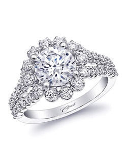 This gorgeous engagement ring features a generous diamond halo and split shank covered in diamonds. The sides of the ring are scalloped, creating a truly unique design. Created for a 1.5CT center stone.