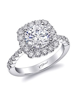 This glamorous engagement ring features a 2CT center stone framed by a cushion shaped diamond halo. Diamonds flow down the shoulders of the ring for added sparkle. Scalloped edging adds a finishing touch and frames the diamonds beautifully.