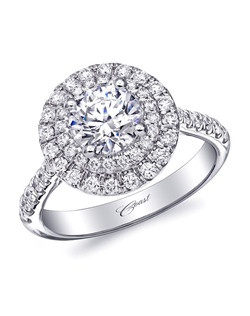 This stunning engagement ring features a double diamond halo surrounding a 1CT center stone, and diamonds on the shoulders of the ring.