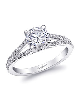An elegant engagement ring featuring a split diamond shank which frames a 1CT center stone. Total diamond weight .21CT, not including center stone.