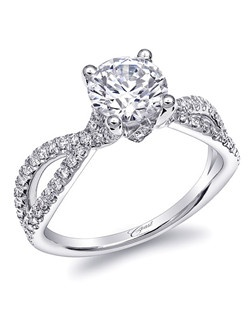 This stunning engagement ring features a criss-crossing split shank of diamonds which curves up to a 1.25CT center stone. Pave diamond details on either side of the head give an extra touch of sparkle.