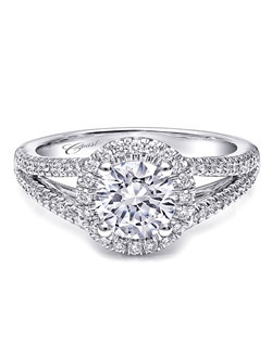 This perfectly refined platinum engagement ring design features a split shank and an elegant round halo encrusted in diamonds. Created for a 1CT center stone.