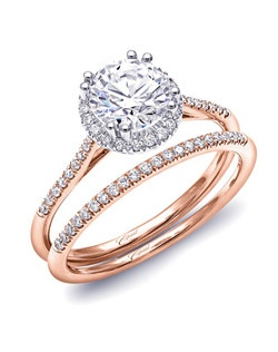 This petite two-tone beauty features a round diamond halo framing the center stone, and diamonds decorating the shoulders of the ring. Standard size created for a 1CT center stone. Shown in rose and white gold with matching rose gold diamond band.