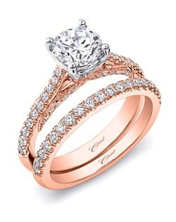 This captivating rose and white gold engagement ring features ribbons of pave set diamonds in the gallery, and diamonds decorating the rose gold shank. A matching diamond band in rose gold completes the look for a unique wedding set. Standard size created for a 1CT center stone.