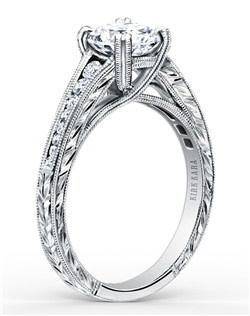 This timeless classic is a tapered engagement ring from the Stella collection. It features 0.25 ctw of diamonds. The signature handcrafted details include wheat hand engravings and milgrain edging. The center 1 carat round stone (shown) is a customized option. Engagement ring is also available as shown featuring blue sapphires (K1140BDC-R) or pink sapphires (K1140VDC-R). Matching wedding band is also available as shown featuring all diamonds (K1140D-B), blue sapphires (K1140BD-B) or pink sapphires (K1140VD-B).