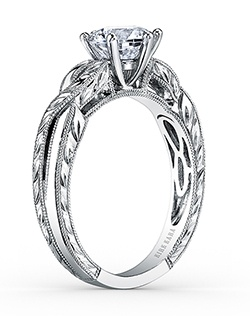 This romantic design is a classic solitaire engagement ring from the Pirouetta collection. It features . The signature handcrafted details include wheat hand engravings and milgrain edging. The center 1 carat round stone (shown) is a customized option. Matching wedding band is also available as shown (K1220-B).