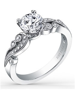 Award winning design. This whimsically chic, artistic design is an engagement ring from the Angelique collection. It features 0.14 ctw of diamonds and signature handcrafted milgrain edging. The center 1 carat round stone (shown) is a customized option. Engagement ring is also available as shown for a pear-shaped center (K1265DE-R). Matching wedding band is also available as shown (K1250D-B).