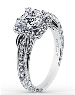 This elegant design is a halo engagement ring from the Pirouetta collection. It features 0.25 ctw of diamonds. The signature handcrafted details include wheat hand engravings, milgrain edging, peek-a-boo diamonds and signature filigree. The center 1 carat cushion stone (shown) is a customized option. Matching wedding band is also available as shown featuring all diamonds (K1170D-B), rose gold (K1170DP-B), yellow gold (K1170DY-B), blue sapphires (K1170SD-B), or pink sapphires (K1170VD-B).