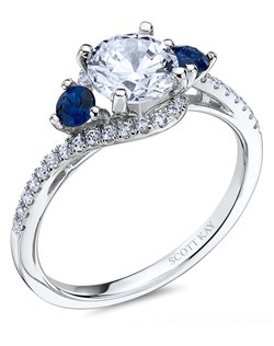 The significance of Luminaire is encrypted within its encircled galaxy of brilliance. This elegant 14K white gold Scott Kay ring has a 0.53ctw and a 1ct round center stone diamond with sapphire gemstones. Also available in platinum, 18K white or yellow gold, 14K yellow gold, and palladium.