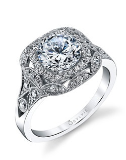 This unique vintage white gold diamond engagement ring features a 1.50 carat round diamond center with a total of 0.48ct carats in our signature cushion halo and bezel-set diamond embellished shank.