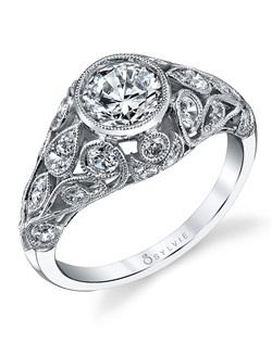 This vintage white gold diamond engagement ring features a 1 carat round diamond center with a total of 0.73 carats in our signature milgrain bezel center and filigree design shank.