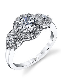This three-stone white gold diamond engagement ring features a 1 carat round diamond center with a total of 0.55 carats in our signature round halo and round side diamonds with polished shank.