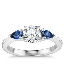 Delicate and elegant, this engagement ring features two pear-shaped sapphires set in elegant 18k white gold to complement your center diamond.