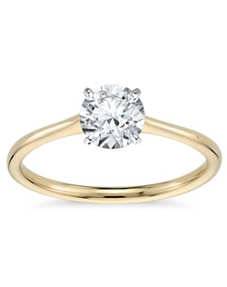 Elegant in simplicity, this petite solitaire engagement ring is crafted in polished 18k yellow gold to create a classic frame for your center diamond.