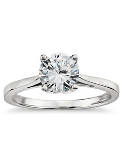 Graceful in design, this classic yet distinctive solitaire engagement ring features a cathedral shank and delicate petal prong detailing that will showcase your center diamond. One signature Monique Lhuillier pink sapphire is hand-set on the interior of each engagement setting. Also available in 18K as a special order.