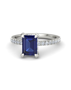 Simply stunning, this ring's brilliant, emerald-cut gem is perfectly complemented by a delicate and feminine band with gems half-way around the finger. More gems surround the side of the center stone. It is carefully handcrafted in your choice of 23 gems and 9 metals.
