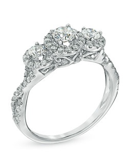 "A promise that you'll love her yesterday, today and tomorrow, this three stone framed ring is a glimmering, glistening gift of love. Fashioned in 14K white gold, this ring features a trio of round diamonds - the largest an impressive 1/3 ct. - each framed with smaller accent diamonds, aligned across the top of the polished diamond-lined twisting shank. The inside of the ring is rounded for comfort. This 1ct. t.w. diamond style is finished with two accent diamonds and the words ""Past, Present, Future"" engraved on the inside of the shank to remind her of your promise to be by her side, always."