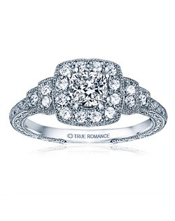 An elegant design, this diamond engagement ring showcases a prong-set diamond halo that crowns the Cushion shaped center stone within a vintage styled design. This style accommodates various center stone sizes & shapes. Available in Platinum, as well as 18K and 14K White, Yellow or Rose Gold. Priced as shown 0.24cts 14K WG