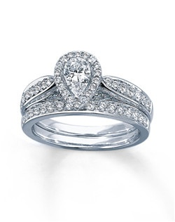 A pear-shaped diamond is framed in round white diamonds in this awe-inspiring engagement ring for her. Additional round diamonds are set in the band of 14K white gold to complete the look. The stunning matching wedding band features a line of glittering round diamonds. The bridal set has a total diamond weight of 1 1/5 carats.