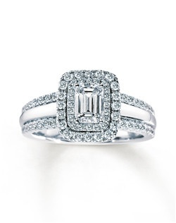 Two rows of round diamonds frame a stunning emerald-cut diamond at the center of this remarkable engagement ring for her. Two rows of additional round diamonds edge each side of the 14K white gold band. The ring has a total diamond weight of 1 1/2 carats.