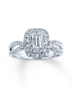 Two rows of round diamonds frame a stunning emerald-cut diamond at the center of this remarkable engagement ring for her. Two rows of additional round diamonds set in 14K white gold crisscross to create the dazzling band. The ring has a total diamond weight of 1 carat.